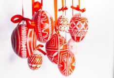Le uova di Pasqua del primo piano con il modello ucraino piega appendono sui nastri rossi su fondo bianco Uova tradizionali ucrai Fotografie Stock