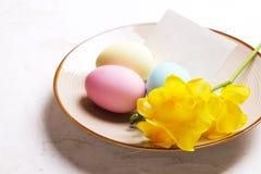 Le uova di Pasqua differenti di colore pastello hanno risieduto e sistemato nella bella composizione con i wildflowers bianchi Ca fotografie stock libere da diritti