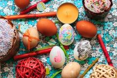 Le uova di Pasqua dipinte sul blu fiorisce il fondo nello stile rustico Fotografie Stock