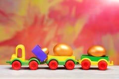 Le uova di Pasqua dorate nelle coperture metalliche sull'automobile del camion giocano Immagini Stock Libere da Diritti
