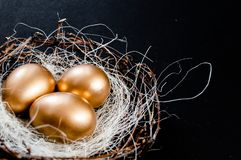 Le uova di Pasqua dorate in uccelli annidano sopra fondo rustico Copyspace del fondo dell'estratto di concetto di festa di Pasqua immagini stock libere da diritti