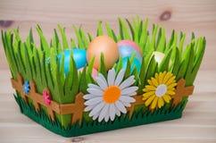 Le uova di Pasqua felici in un canestro annidano sul di legno Immagini Stock Libere da Diritti