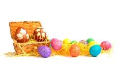 Le uova di Pasqua nella scatola di legno ed uova di Pasqua variopinte vicino alla scatola in fieno Fotografia Stock