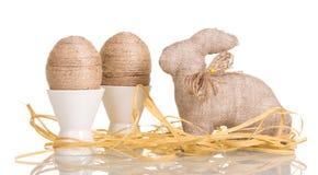 Le uova di Pasqua in tazze con corda si sono intrecciate, coniglietto, i nastri, isolat Fotografia Stock Libera da Diritti
