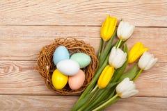 Le uova di Pasqua in uccelli annidano con i tulipani variopinti Immagini Stock