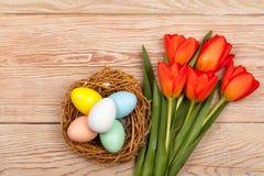 Le uova di Pasqua in uccelli annidano con i tulipani variopinti Fotografia Stock