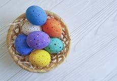 Le uova di Pasqua in un canestro, paglia, bianco di legno hanno dipinto lo spazio di primavera Immagini Stock Libere da Diritti