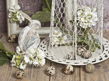 Le uova di Pasqua in una gabbia, balzano fiori bianchi, le uova di quaglia, coniglietti bianchi Immagini Stock