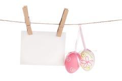 Le uova di Pasqua variopinte e la foto in bianco incorniciano l'attaccatura sulla corda Fotografia Stock