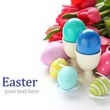 Le uova di Pasqua variopinte ed i tulipani rosa sopra bianco con il campione mandano un sms a Fotografia Stock