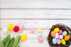 Le uova di Pasqua variopinte in nido con il tulipano fioriscono sul fondo di legno rustico delle plance Immagine Stock