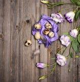 Le uova di quaglia di Pasqua con i fiori di eustoma ed il mestiere porpora incartano la o Immagine Stock Libera da Diritti