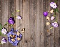 Le uova di quaglia di Pasqua con i fiori di eustoma ed il mestiere porpora incartano la o Fotografia Stock Libera da Diritti