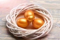 Le uova dorate dipinte di pasqua in uccello annidano su fondo variopinto Fotografia Stock