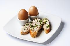 Le uova ed il panino aperto con pane e la casa tostati hanno prodotto il burro di acciuga aromatico Fotografia Stock