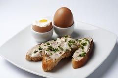 Le uova ed il panino aperto con pane e la casa tostati hanno prodotto il burro di acciuga aromatico Immagini Stock