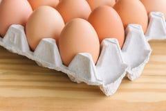 Le uova fresche in scaffale dell'uovo hanno messo sopra la tavola di legno Prepari le uova f del pollo Immagini Stock Libere da Diritti
