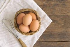 Le uova fresche in vecchio canestro di legno hanno messo sopra il tovagliolo bianco Prepari fresco Fotografia Stock
