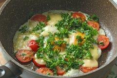Le uova fritte fresche sono cucinate in una padella, con i pomodori, il formaggio ed i verdi Piatti vegetariani Alimento sano lum immagini stock libere da diritti