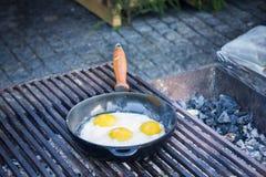 Le uova fritte hanno fritto in una pentola sulla griglia Immagine Stock
