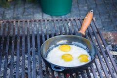 Le uova fritte hanno fritto in una pentola sulla griglia Fotografie Stock
