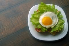 Le uova fritte interpongono con bacon e formaggio immagine stock