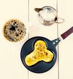 Le uova fritte nel divertimento si formano del pene dell'uomo in una padella con caffè Immagini Stock