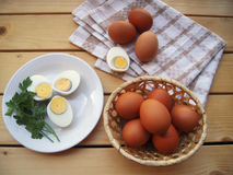 Le uova hanno tagliato su un piatto, nel canestro e sull'asciugamano di cucina su una tavola di legno, styl rustico immagine stock