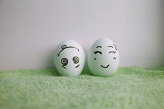 Le uova sono divertenti con i fronti che tutte su si dirigono su verde Fotografie Stock Libere da Diritti