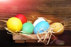 Le uova variopinte di Pasqua in canestro di legno con paglia annidano Fotografia Stock