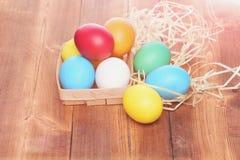 Le uova variopinte di Pasqua in canestro di legno con paglia annidano Fotografia Stock Libera da Diritti