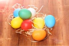 Le uova variopinte dipinte di pasqua con paglia annidano su fondo di legno Fotografia Stock