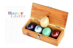 Le uova variopinte in scatola di legno su fondo bianco con il campione mandano un sms a Fotografie Stock