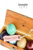 Le uova variopinte in scatola di legno su fondo bianco con pasqua felice etichettano Fotografia Stock Libera da Diritti