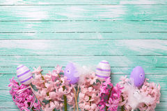 Le uova viola decorative ed i giacinti rosa fiorisce su turchese Immagini Stock