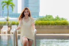 Le upp den unga asiatiska kvinnan på simbassängen Royaltyfri Bild