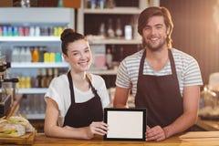 Le uppassaren och servitrins som använder den digitala minnestavlan på räknaren royaltyfri fotografi