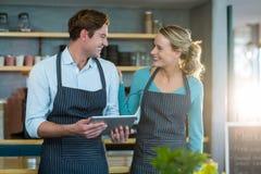 Le uppassaren och servitrins som påverkar varandra, medan genom att använda den digitala minnestavlan royaltyfri fotografi
