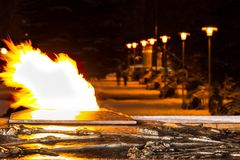 Le ustioni eterne della fiamma nella penombra della notte e nella distanza una possono vedere un vicolo illuminato dalle lampade  immagini stock libere da diritti