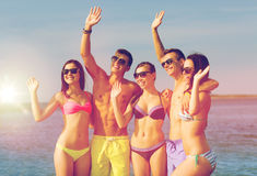Le vänner i solglasögon på sommarstranden Arkivfoton