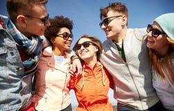 Le vänner i solglasögon som skrattar på gatan royaltyfria foton