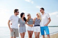 Le vänner i solglasögon som talar på stranden Arkivfoton