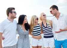 Le vänner i solglasögon som talar på stranden Arkivbilder