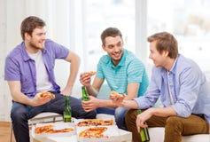 Le vänner med öl och pizza som ut hänger arkivfoto