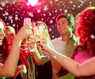Le vänner med exponeringsglas av champagne i klubba Arkivfoton