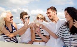 Le vänner med exponeringsglas av champagne på yachten Arkivbild
