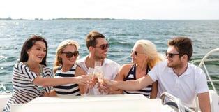 Le vänner med exponeringsglas av champagne på yachten Royaltyfria Bilder
