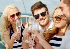 Le vänner med exponeringsglas av champagne på yachten Arkivbilder