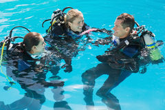Le vänner på dykapparatutbildning i simbassäng Fotografering för Bildbyråer