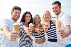Le vänner som äter glass på stranden Fotografering för Bildbyråer